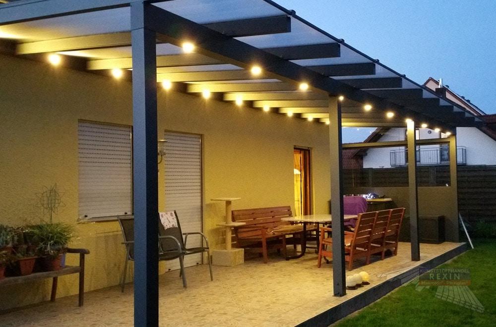 Ein imposantes Alu-Terrassendach REXOclassic 9m x 3,5m in Anthrazit mit Eiskristall-Stegplatten, Seitenkeil & einer REXOcover Protect Seitenwand.