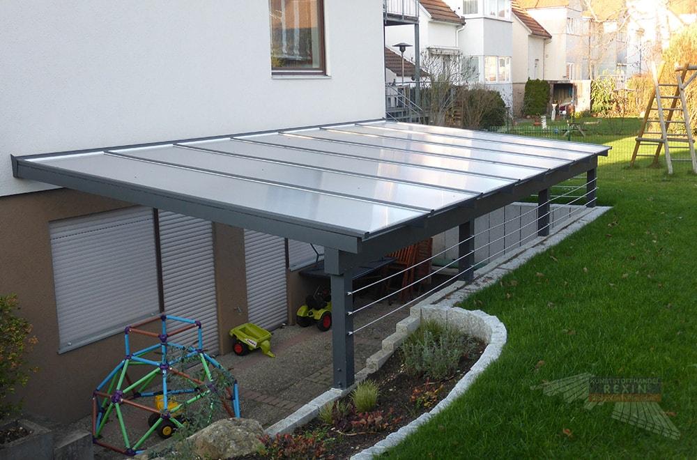 Ein Alu-Terrassendach REXOclassic 7m x 3,85m in Anthrazit und Polycarbonat-Stegplatten. Hier wurden die Pfosten individuell gekürzt, um den Zugang zum Souterrain zu überdachen.