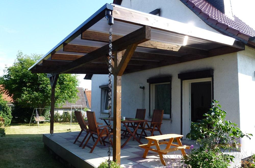 Ein Holz-Terrassendach REXOcomplete 6m x 4 m mit Holzfarbe Palisander und Stegplatten in sanftem Bronzeton.