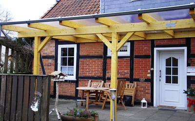 Ein Holz-Terrassendach an einer traditionellen Hausfassade.