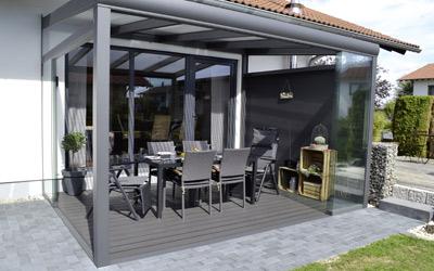 Ein gemütliches Gartenzimmer durch Glasschiebewände und eine Seitenwand.